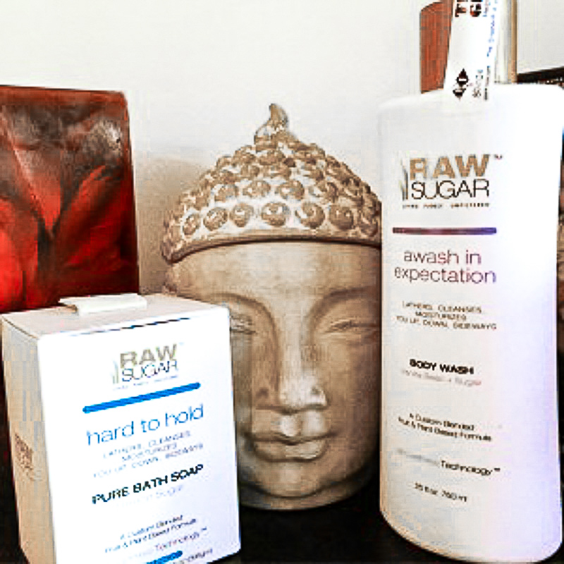 Raw sugar living pure bath soap and raw sugar awash in expectiation body wash with a buddha head in between