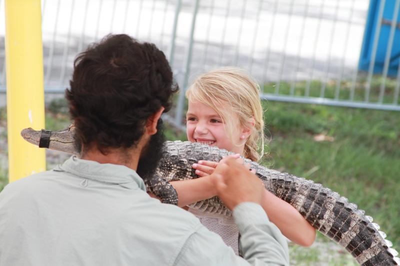 girl holding aligator