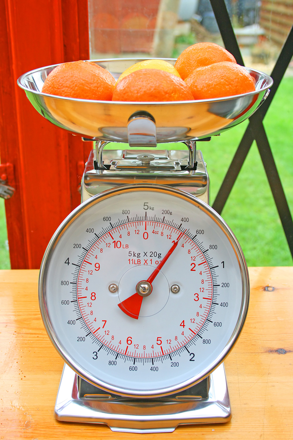 Kitchen scales with fruit in the weighing bowl on a wooden worktop.