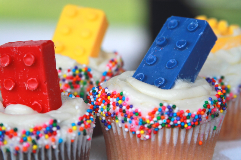 lego cupcakes with lego candy molds on top and sprinkles on the side