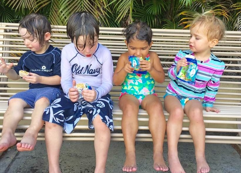 4 kids sitting on a bench in their bathing suits eating lucky bars