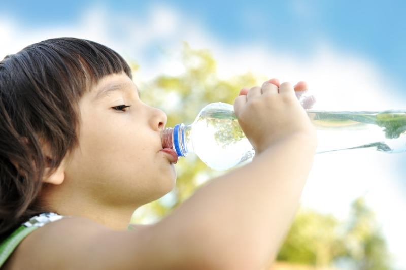 child drinking bottled water