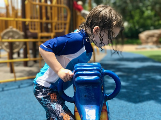 kid in bathing suit playing at park