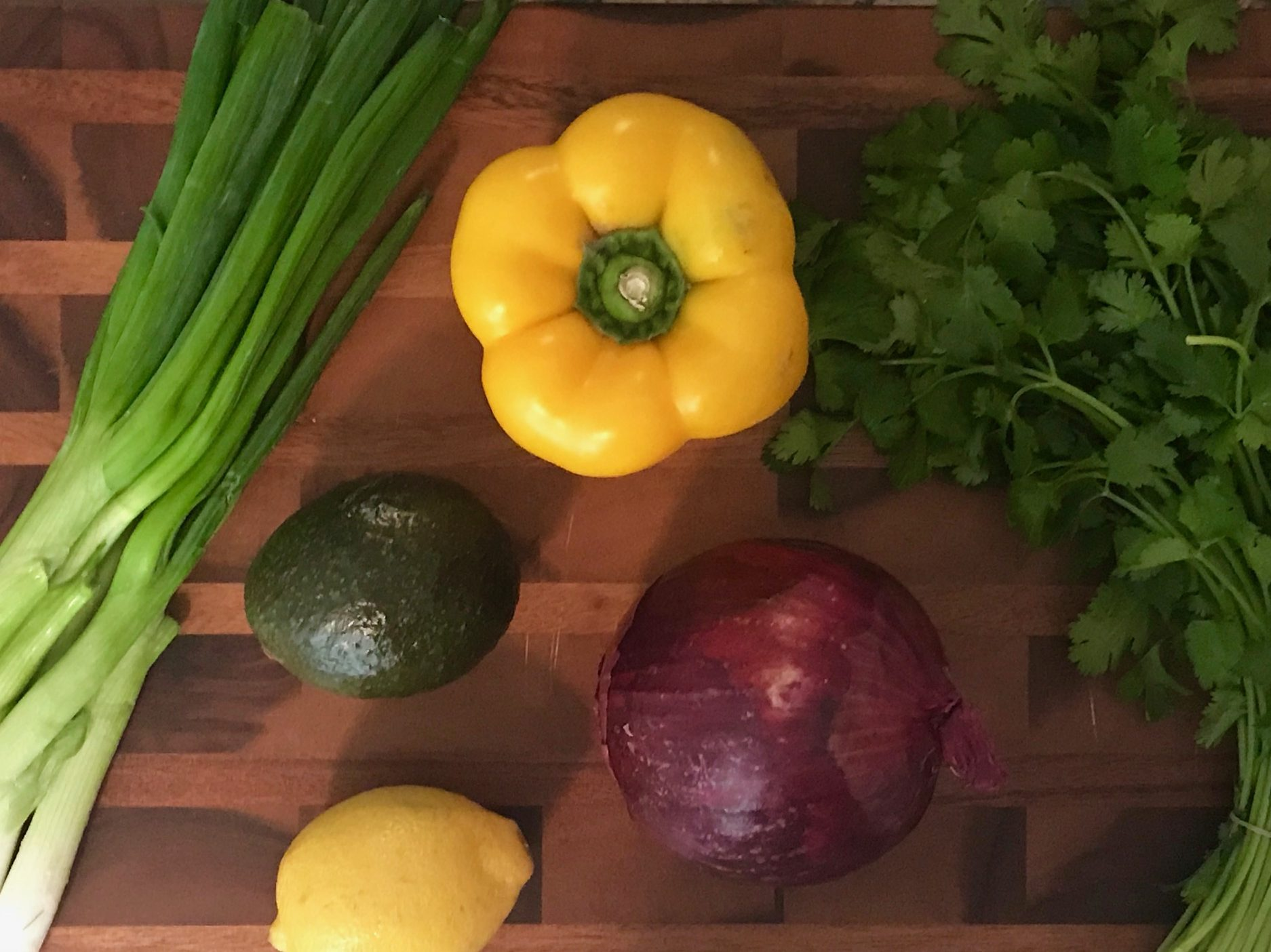 pepper, parsley, avocado, red onion, lemon and spring onions on a cutting board