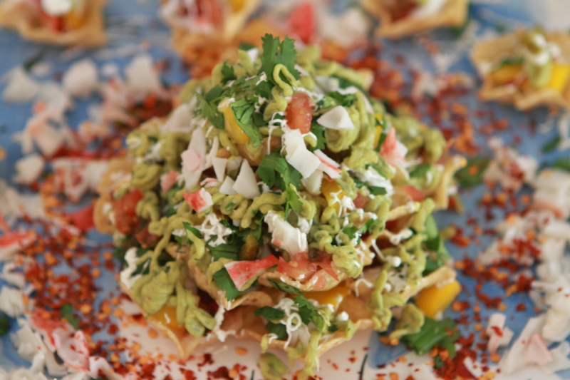 holiday cheeseless and crab nachos on a decorative plate