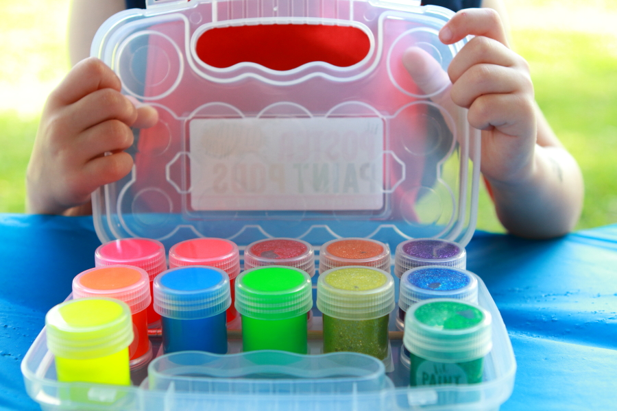 child opening box of colorful paints on blue tablecloth
