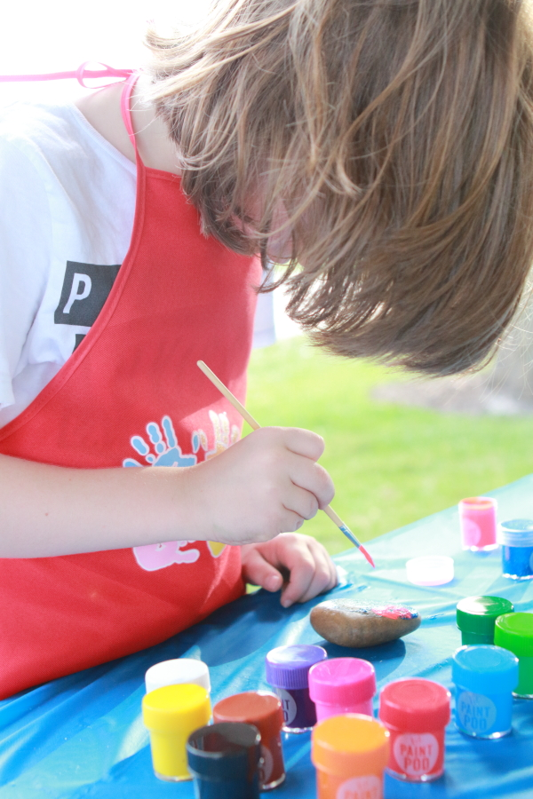 child painting a rock with paints on a table with a blue cloth