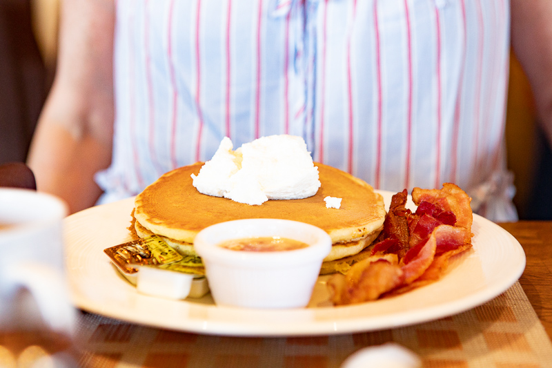 plate of pancakes and bacon with syrup