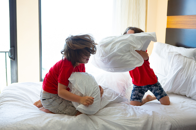 two boys having a pillow fight on a bed