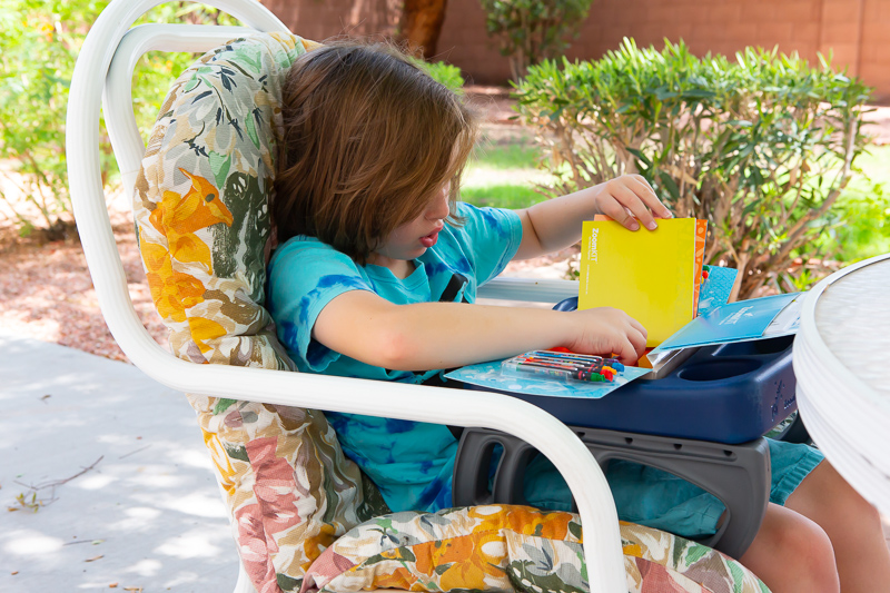 boy sitting in a chair with crayons