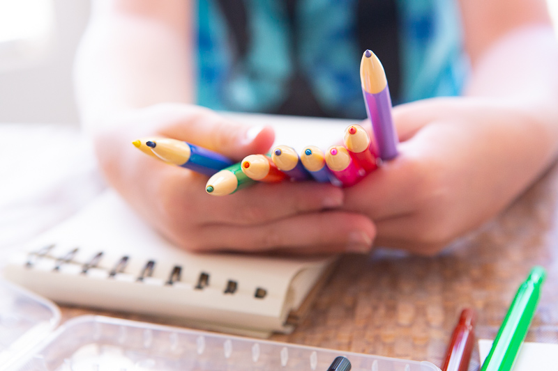 child holding colored pencils