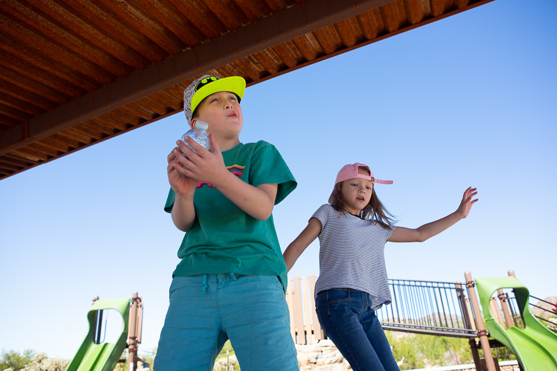 two kids playing on a landscape structure playground