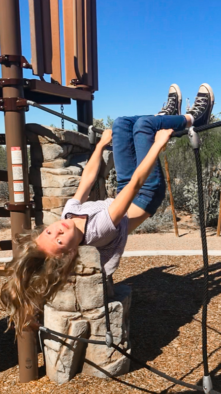 girl hanging upside down on wire on playground