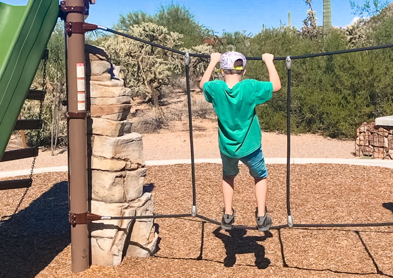 kid hanging on a rope attached to play structure