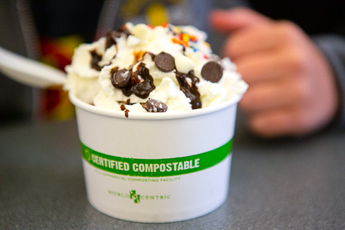 ice cream with whipped cream with sprinkles and chocolate chips in a compostable cup