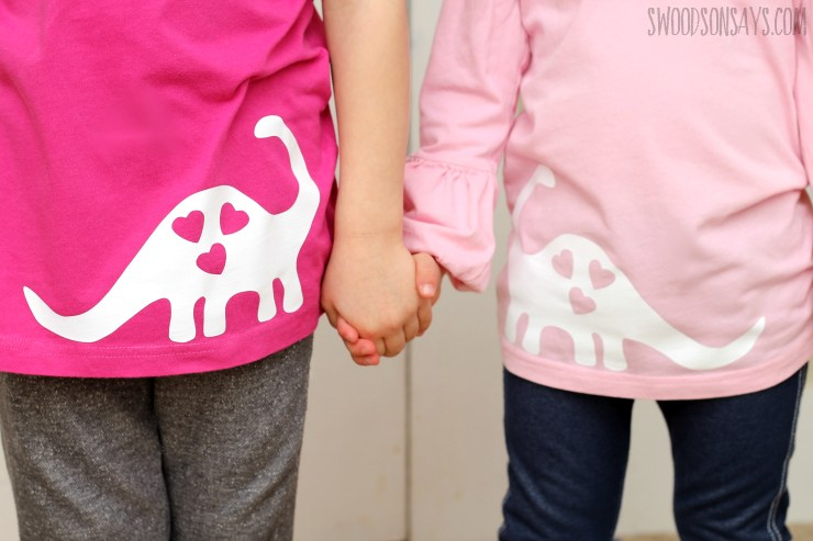 two children  holding hands with pink shirts with white dinasoars on
