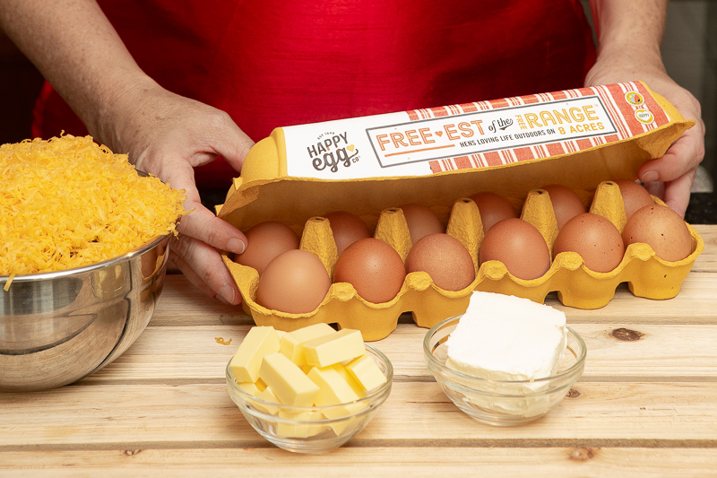hands opening a box of eggs next to a bowl of grated cheese butter and cream cheesee