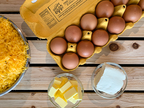 open box of carton of eggs next to bowl of cheddar cheese butter and cream cheese