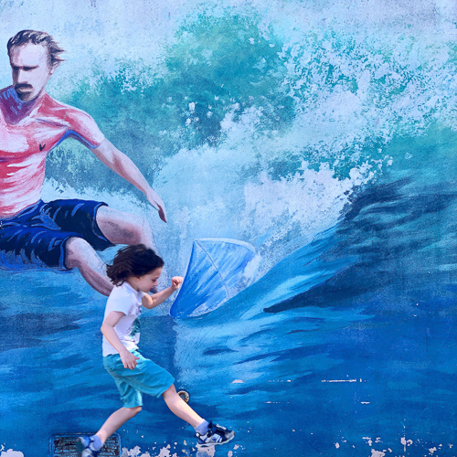 boy running in front of a picture of a guy surfing at the Surfing Museum