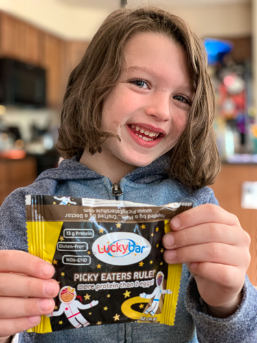 child holding a chocolate luckybar smiling