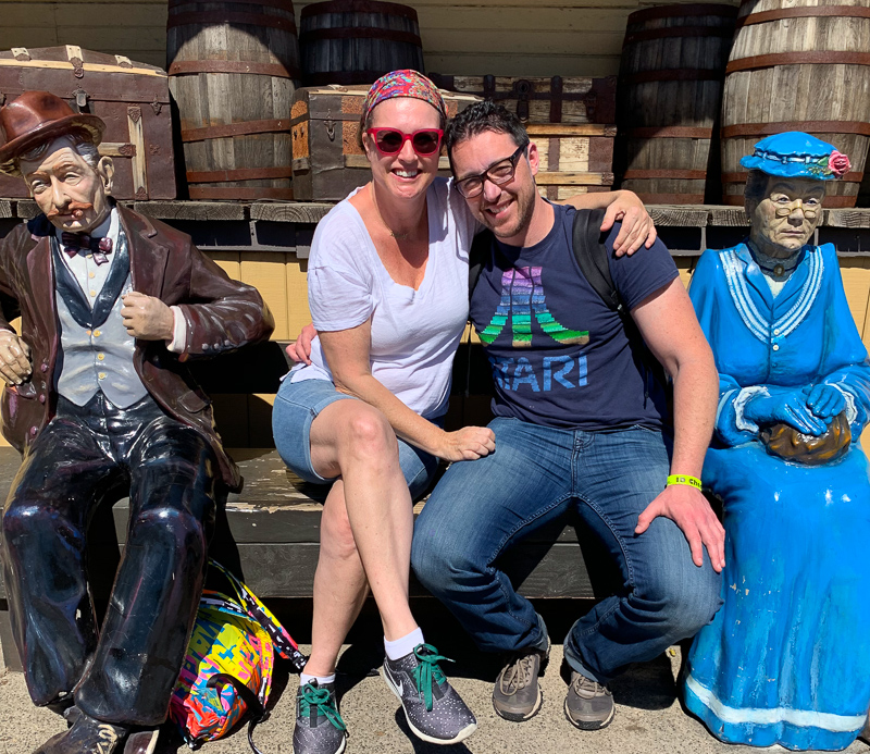 husband and wife sitting on the bench smiling at Knottsberry Farm with a statue of a man and woman