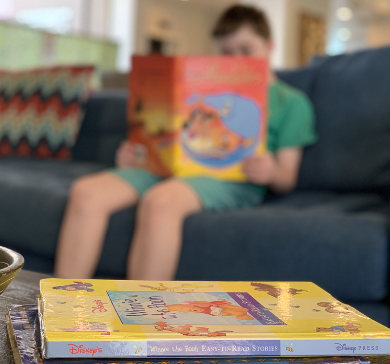 Child reading Disney books on the couch in the actiivty center at the Peacock Suites in Ananheim California