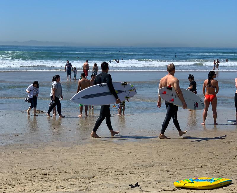 Surfers walking on the beach on Huntington Beach California
