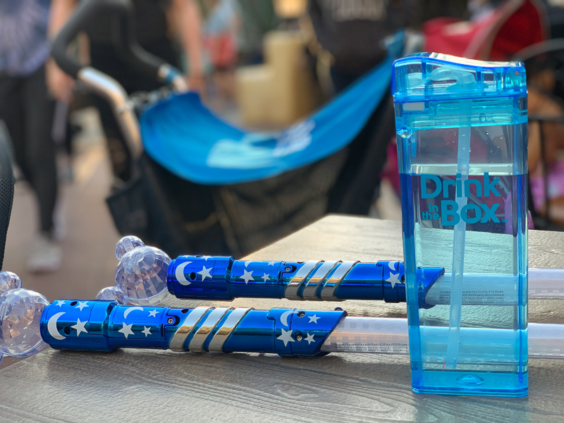 blue drink box on table next to 2 blue mickey mouse light sabers