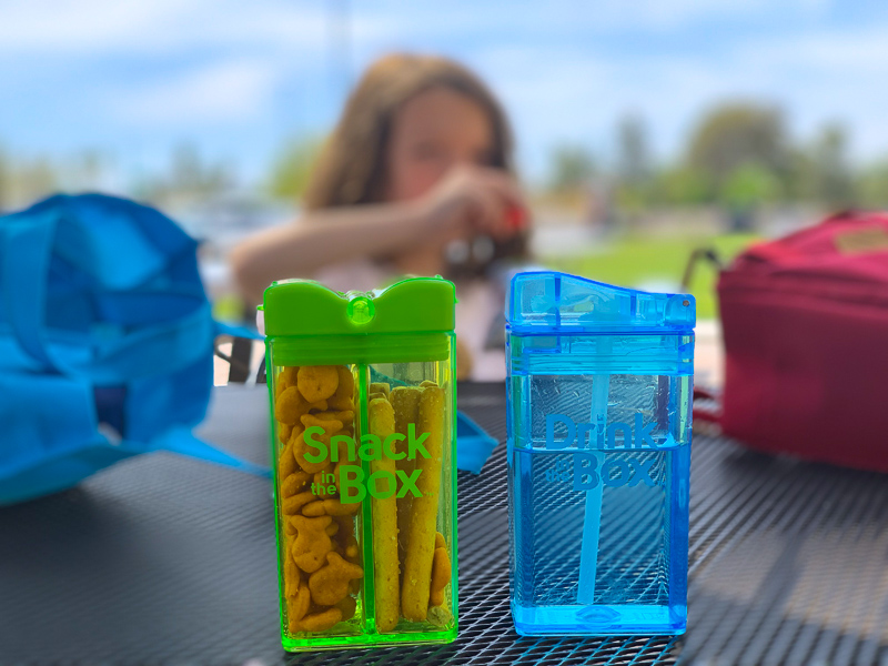 green snack box and blue drink box with kids at the park