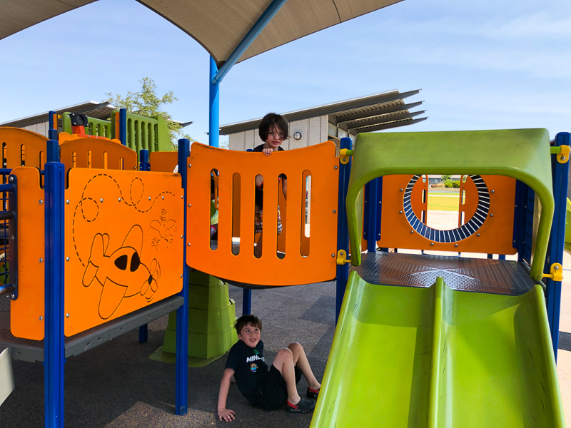 two boys playing at a play structure