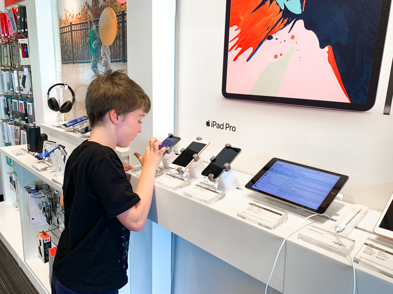boy looking at cell phones in a shop