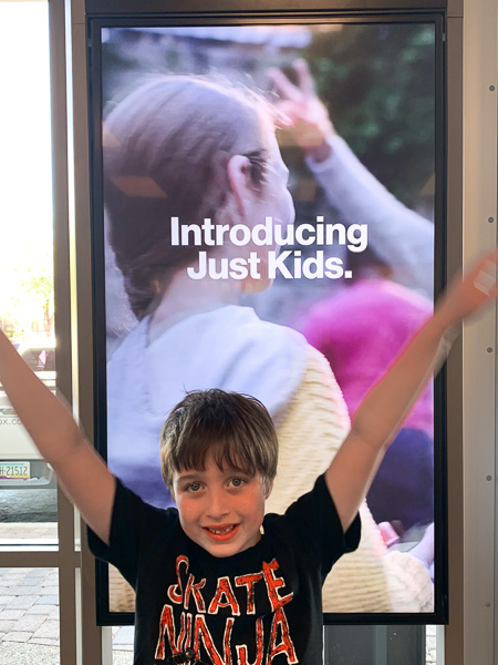 boy standing in front of a verizon sign with arms up smiling