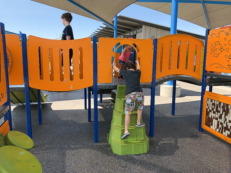 two boys playing on play structure