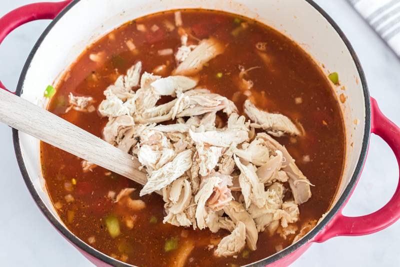 shredded chicken being added to soup base