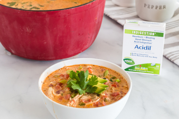 red bowl of enchilada soup with small bowl of soup and acidil next to it