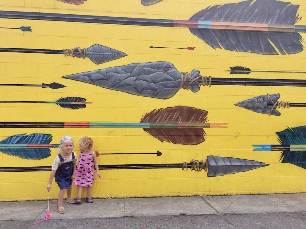 two little girls in front of street art