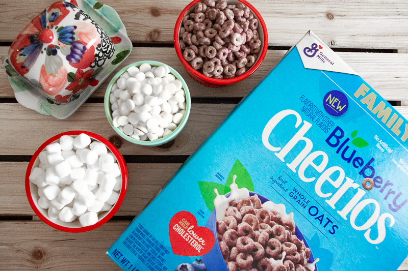box of blueberry cheerios with a bowl of blueberry cheerios, a bowl of white chocolate chips, a bowl of marshmallows and butter.