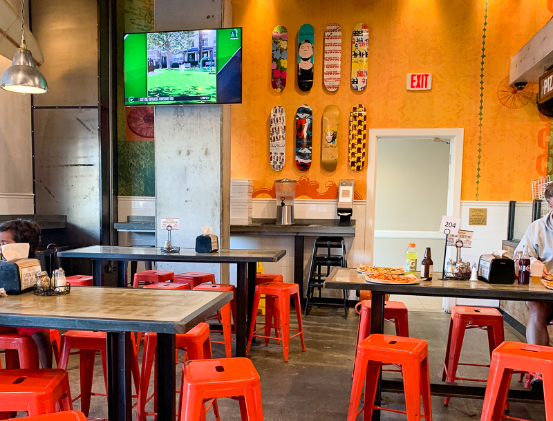 pizzaria restaurant with tables and orange chairs and skateboards on the wall