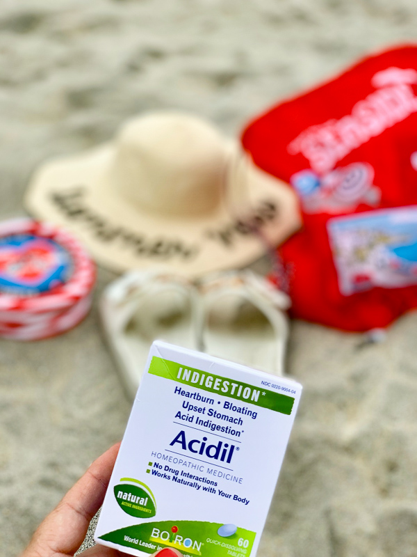 acidil on the beach with hat and bags