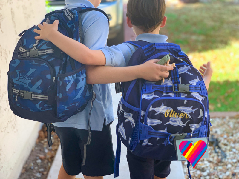 two brothers with their arms around eachother holding backpacks