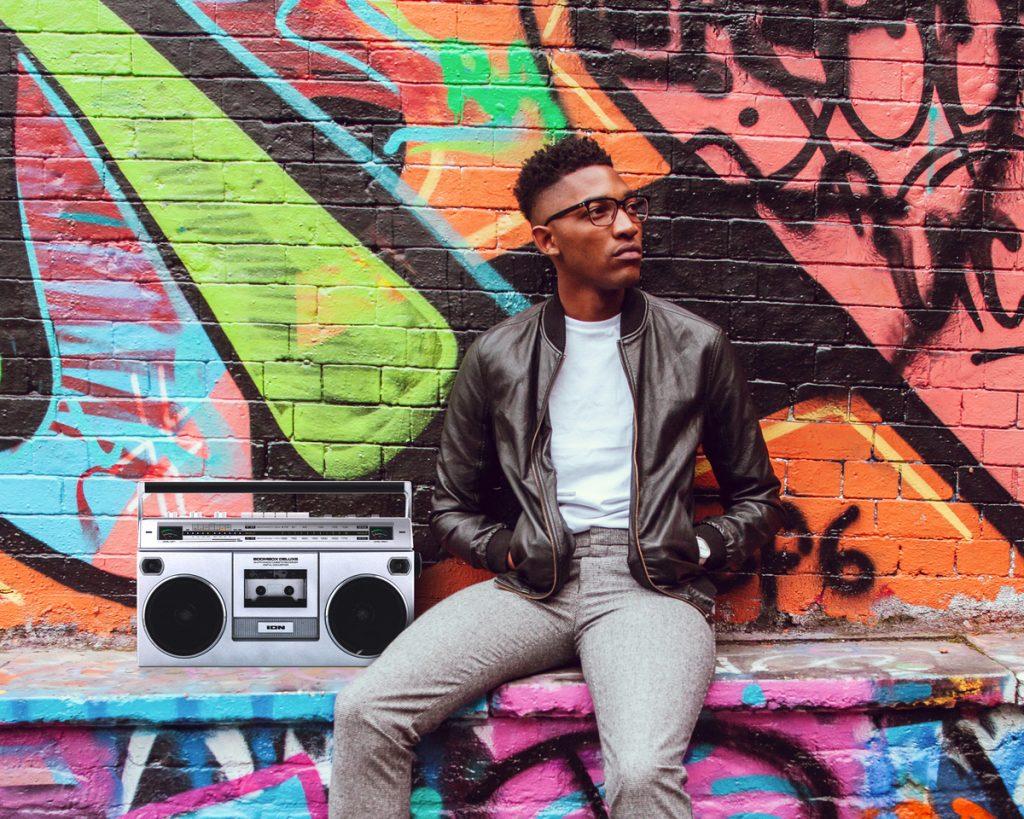Young black man sitting on a graffiti wall next to a boombox
