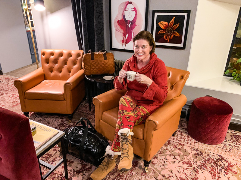 girl in a holiding a cup on a chair in a hotel