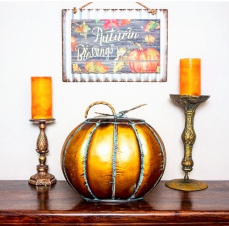 Fall layout of candles and a pumpkin and a hanging picture