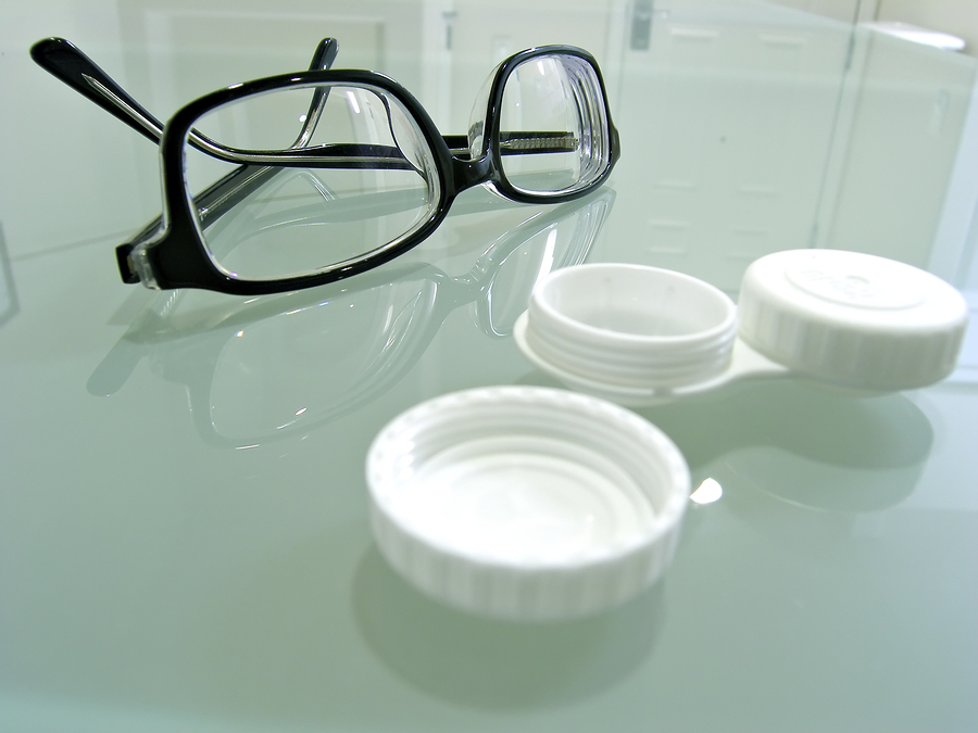 black eye glasses next to an empty contact lens holder