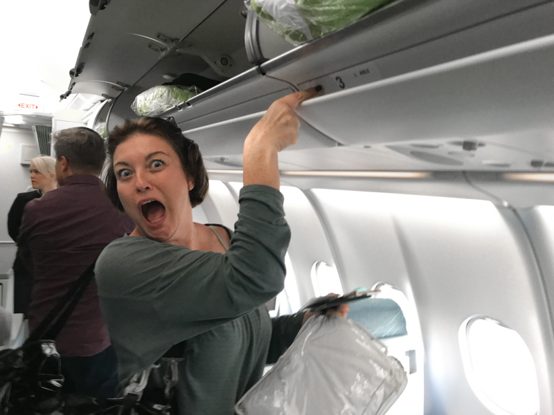 woman pointing to the overhead bin