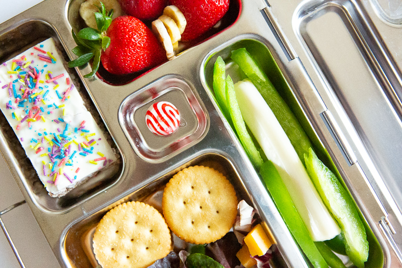 lunch box with pepper, crackers, cheerios bar and mint