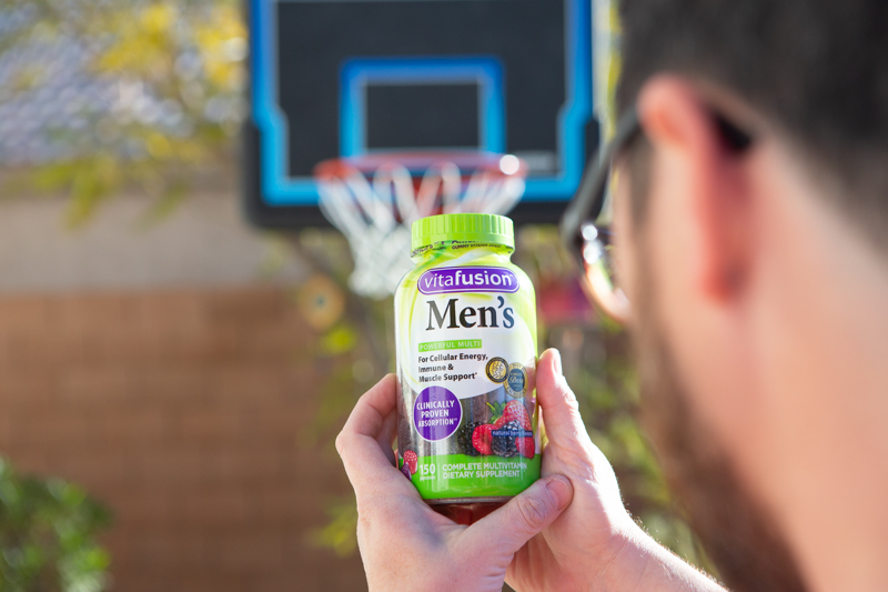 man holding vitafusion gummies in front of a basketball hoop