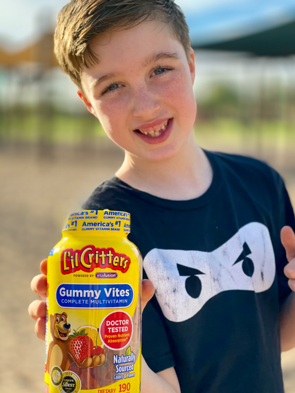 boy smiling while holding a bottle of vitafusion l'il critters gummy vites