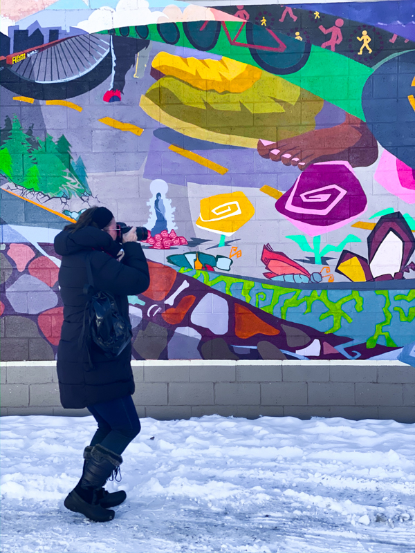 woman wearing black taking a picture of a mural in the snow