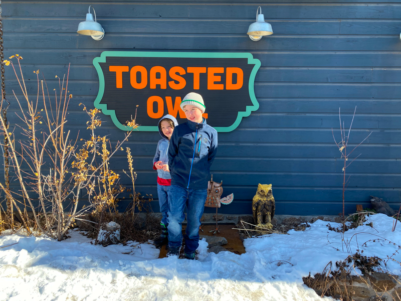 two boys standing outside in front of a sign saying Toasted Owl